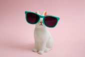 a cute white plastic bunny wearing sunglasses on a pink background.'nMinimal color still life photography