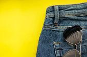 sunglasses in back pocket of blue jeans