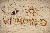 Vintage photo, Sunglasses, inscription vitamin D and shape of sun made of amber stones on sand at beach, concept of vacation time and prevention of vitamin D deficiency