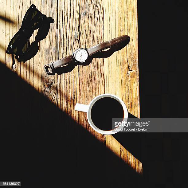 Sunglasses, Wristwatch And Mug Of Coffee On Wooden Table