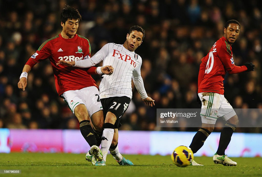 Sung-Yueng Ki (L) of Swansea City and Kerim Frei (R) of Fulham challenge for the ball during the Barclays Premier League match between Fulham and Swansea City at Craven Cottage on December 29, 2012 in London, England.