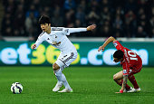 SungYueng Ki of Swansea City goes past Philippe Coutinho of Liverpool during the Barclays Premier League match between Swansea City and Liverpool at...