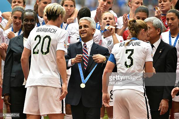 Sunil Gulati the president of the United States Soccer Federation prepares to place a medal on Abby Wambach and Christie Rampone of the United States...