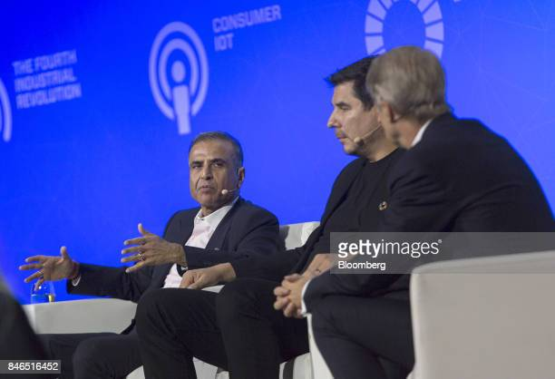 Sunil Mittal chairman of Bharti Airtel Ltd left speaks as Marcelo Claure chief executive officer of Sprint Corp center listens during the Mobile...