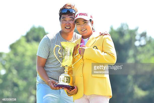 SunJu Ahn and her husband SungHo Kim of South Korea poses with the trophy after winning the Century 21 Ladies Golf Tournament 2015 at the Izu Daijin...