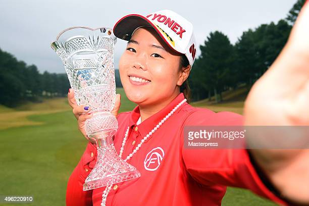 SunJu Ahn of South Korea imitates a 'selfie' as she poses with the trophy after winning the TOTO Japan Classics 2015 at the Kintetsu Kashikojima...