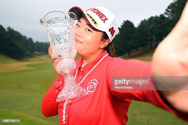 SunJu Ahn of South Korea imitates a 'selfie' as she poses with the trophy after winning the TOTO Japan Classics 2015 at the Kintetsu Kashikojima...