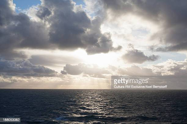 Sunlight breaking through storm clouds over sea