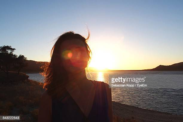 Sunlight Falling On Face Of Woman Standing At Beach