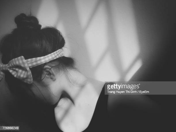 Sunlight Falling On Woman Wearing Headband With Tied Bow By Wall
