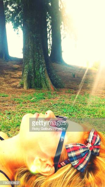 Sunlight Falling On Woman Wearing Sunglasses While Lying At Park