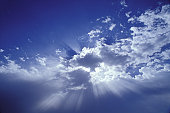 Sunlight Filtered Through Clouds In A Blue Sky