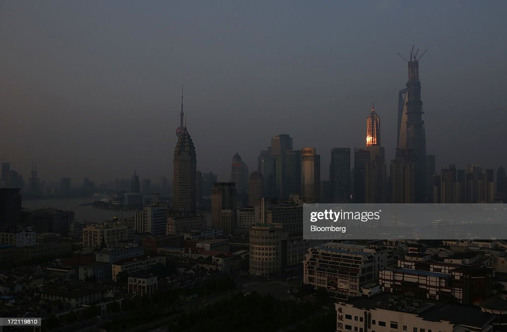 Sunlight is reflected on the Jin Mao Tower as it stands next to other buildings in the Lujiazui district of Shanghai, China, on Sunday, June 30, 2013. China's President Xi Jinping said officials shouldn't be judged solely on their record in boosting gross domestic product, the latest signal that policy makers are prepared to tolerate slower economic expansion. Photographer: Tomohiro Ohsumi/Bloomberg via Getty Images