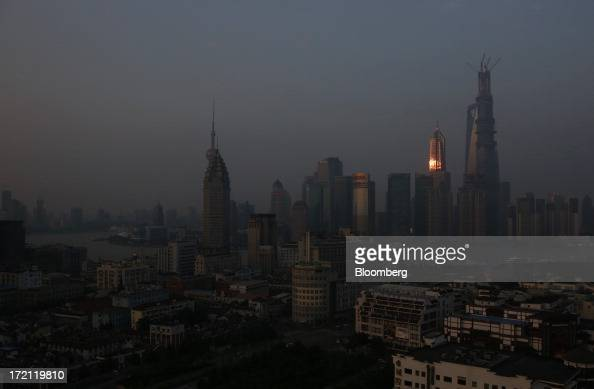 Sunlight is reflected on the Jin Mao Tower as it stands next to other buildings in the Lujiazui district of Shanghai China on Sunday June 30 2013...
