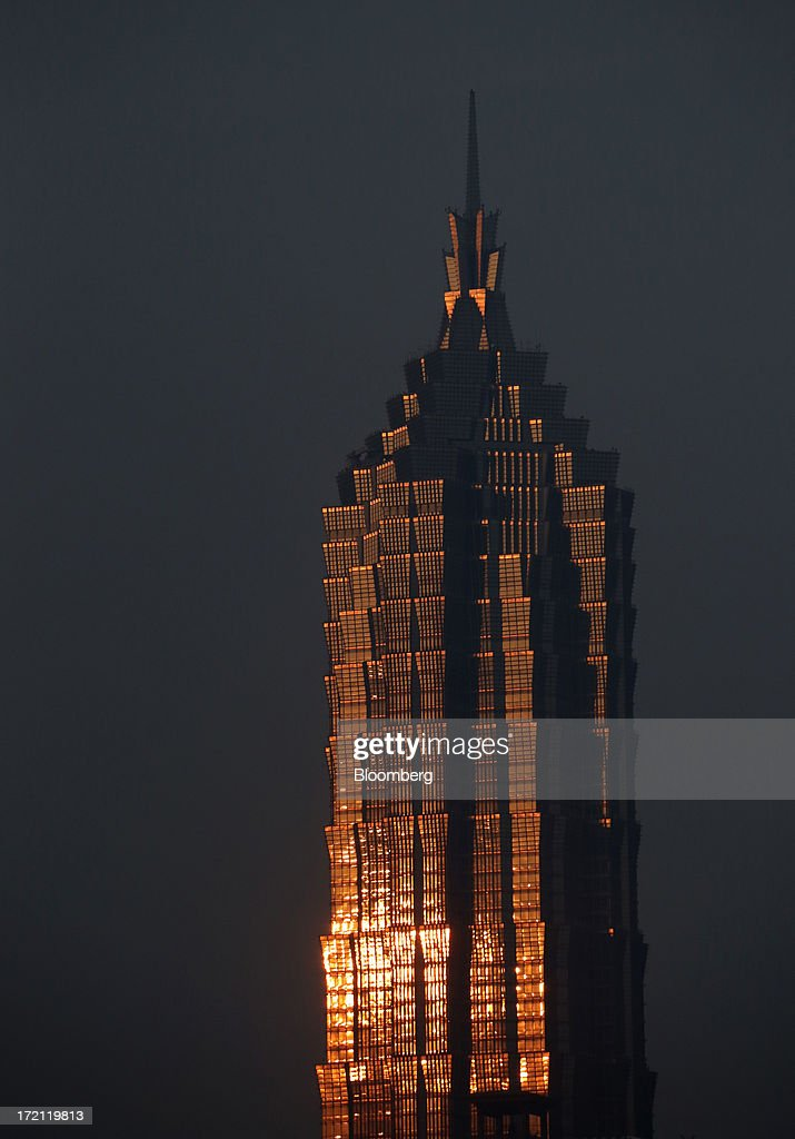 Sunlight is reflected on the Jin Mao Tower in the Lujiazui district of Shanghai, China, on Sunday, June 30, 2013. China's President Xi Jinping said officials shouldn't be judged solely on their record in boosting gross domestic product, the latest signal that policy makers are prepared to tolerate slower economic expansion. Photographer: Tomohiro Ohsumi/Bloomberg via Getty Images