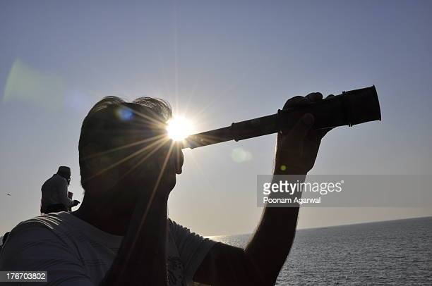Sunlight overhead silhouette of man with telescope