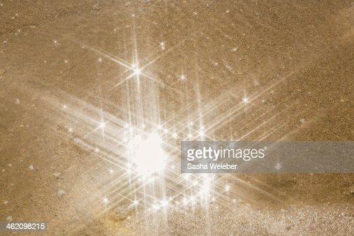 Sunlight reflecting in water on beach