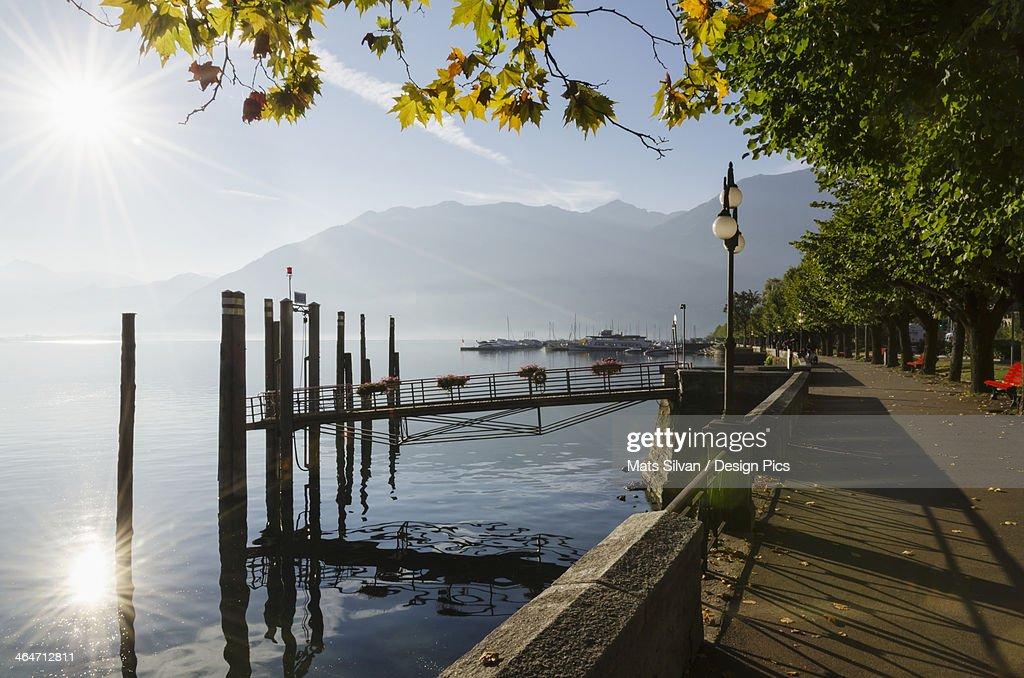 Sunlight Reflecting On Lake Maggiore Beside The Promenade