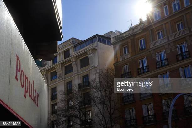 Sunlight shines above residential apartment buildings near a Banco Popular Espanol SA bank branch in Madrid Spain on Friday Feb 10 2017 Banco...
