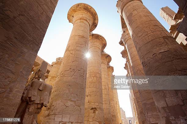 Sunlight sparkles through columns in the Karnak temple hypostyle hall.