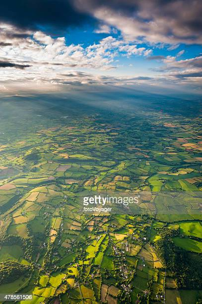 Sunlight streaming through clouds onto idyllic rural landscape aerial vista