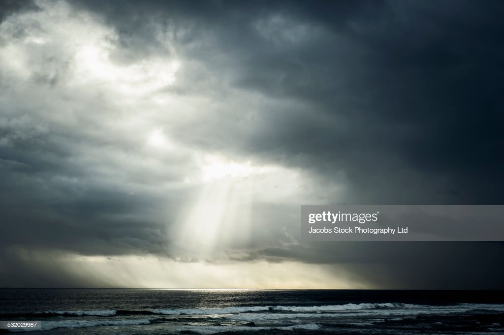 Sunlight streaming through storm clouds over ocean