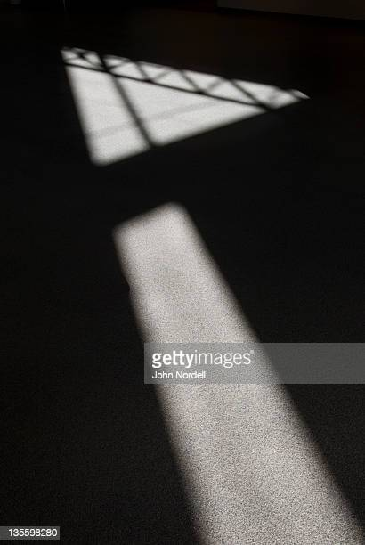 Sunlight streaming through windows forming an arrow shape