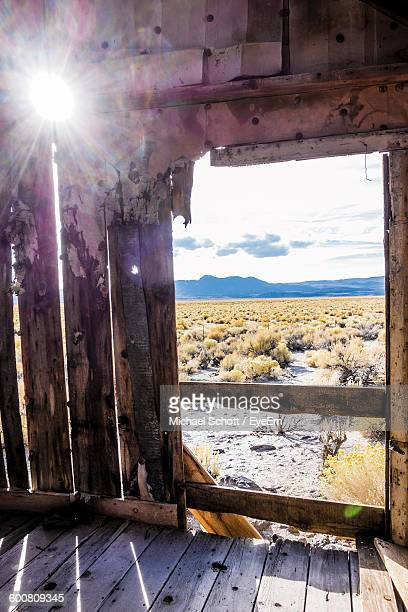 Sunlight Streaming Through Wooden Wall Of Abandoned House