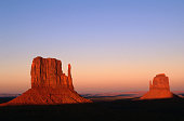 Sunlight strikes the East and West Mitten Buttes, surrounded by barren landscape., Monument Valley Navajo Tribal Park, Arizona, United States of America, North America