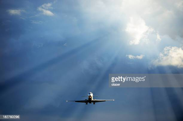 Sunlit airplane flying into sunshine