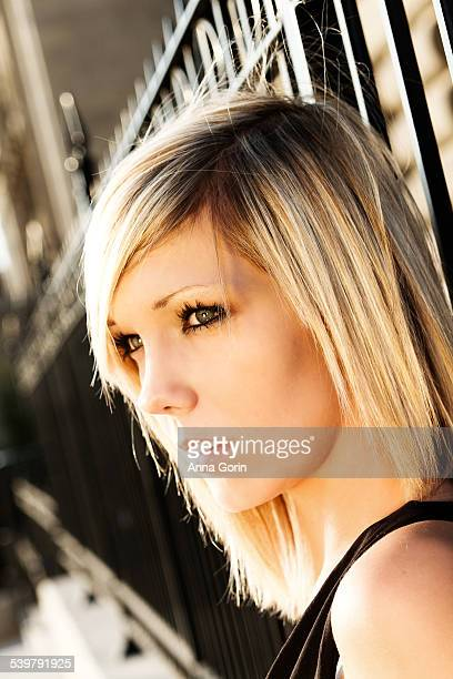 Sunlit blonde model by iron fence, looking away