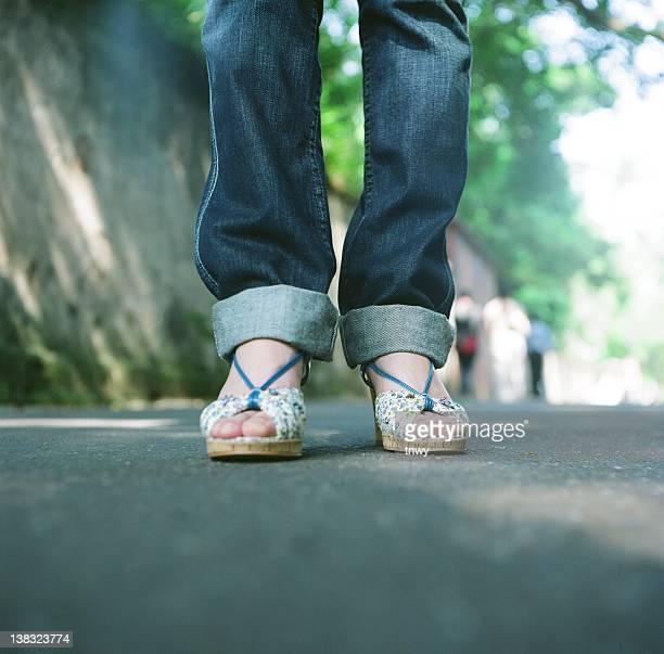 Sunlit blue jeans and blue sandal straps