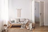 Sunlit living room interior with open door, herringbone parquet floor, natural, beige textiles and white walls