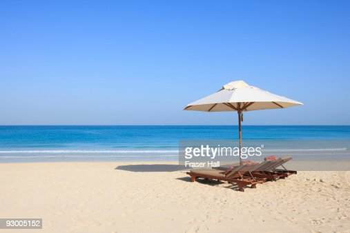 Sunlounger and umbrella on an empty beach : Stock Photo