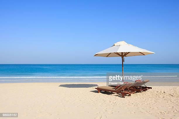 Sunlounger and umbrella on an empty beach