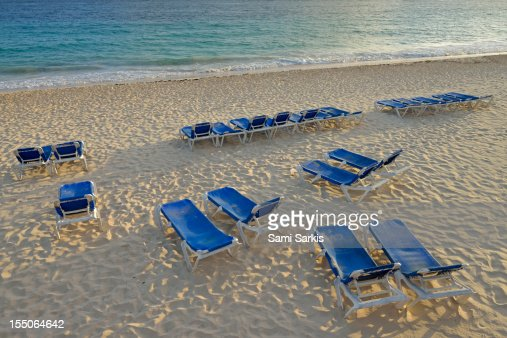 Sunloungers on a tropical beach at sunrise : Stock Photo
