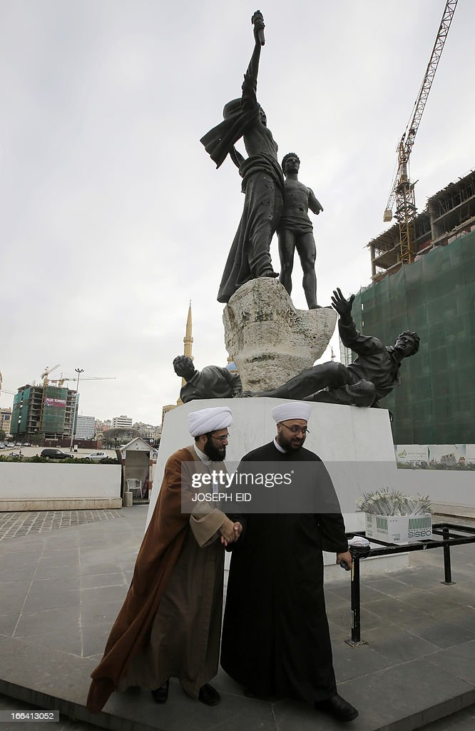 A Sunni and a Shiite cleric shake hands during a gathering of clerics representing the various Lebanese religious communities for peace in central Beirut on the eve of the anniversary of the 1975-1990 civil war on April 12, 2013. AFP PHOTO/JOSEPH EID