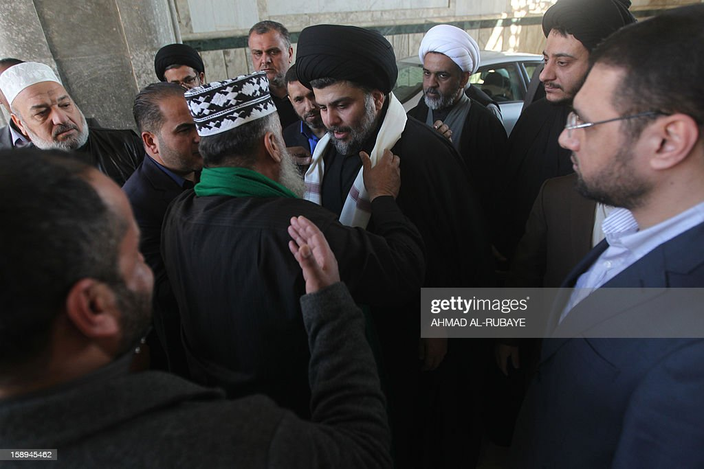 A Sunni Iraqi cleric welcomes Iraq's maverick Shiite cleric Muqtada al-Sadr (C) before the noon Friday prayer in which Sunni and Shiite Muslim worshippers took part together in a gesture of unity at the Abdul Qadir Gilani Mosque in Baghdad on January 4, 2013. In other parts of the country protests in Sunni-majority areas were planned to call for the release of prisoners and criticise Nuri al-Maliki's Shiite-led government.
