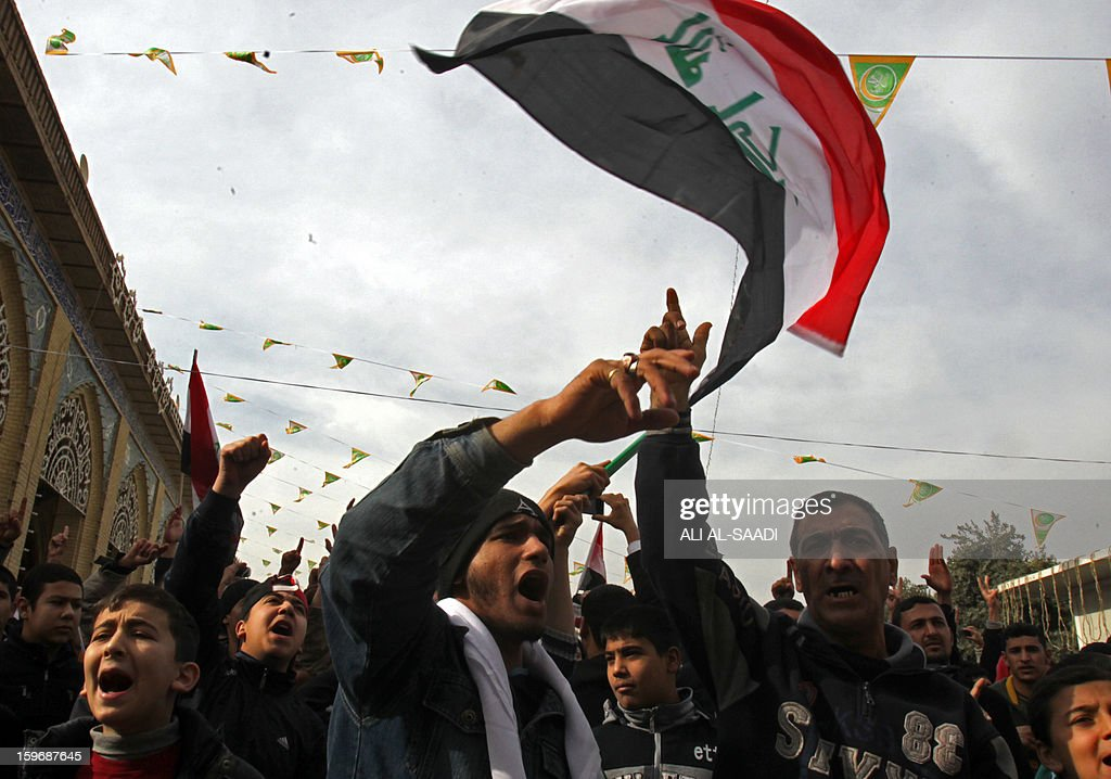 Sunni Muslims shout slogans and wave the old Iraqi flag used between 1991-2004 as they take part in an anti-government demonstration outside the Sunni Abu Hanifa mosque in Baghdad's Adhamiyah district on January 18, 2013. Tens of Iraqi Sunni Muslims took to the streets in Baghdad and other cities after Friday prayers, in another show of discontent with Shi'ite Prime Minister Nuri al-Maliki. AFP PHOTO / ALI AL-SAADI