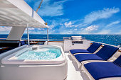 White steel yacht with white deck, nautical blue chairs, whirlpool spa with blue sky and tropical water in the background.