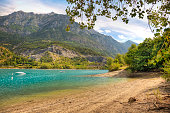 Sunny beach of Lac de Serre-Ponçon lake in France with Alps in background