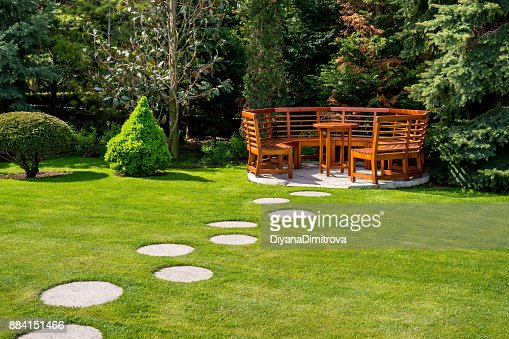 Sunny day in a spring garden with wooden benches : Stock Photo