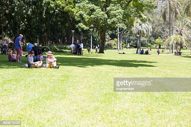Sunny day in city park with people relaxing on grass