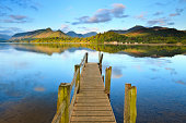 An old jetty on the still water of Derwent Water in Cumbria with the sun shining on the hills in the distance.