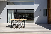 Sunny outdoor entertaining deck with triple glass sliding doors at a new contemporary designed home