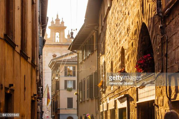 Sunny street with bell tower of the old church in Citta Alta, Bergamo, Lombardy, Italy