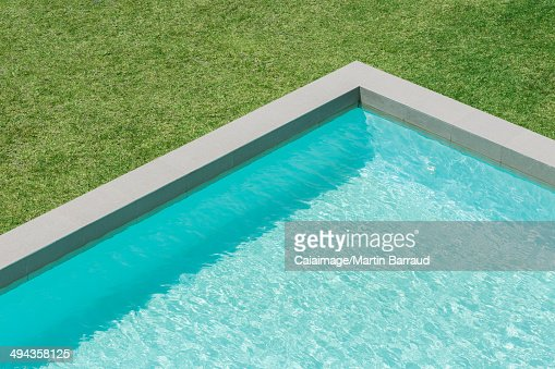 Sunny view of swimming pool in backyard