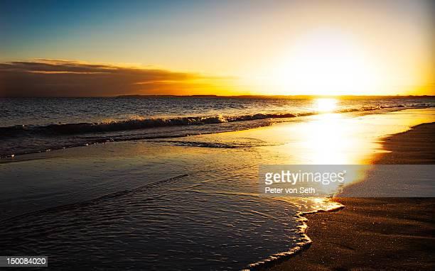 Sunrise above surf at sea
