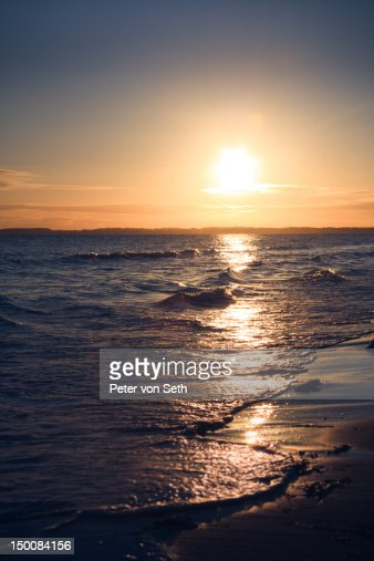 Sunrise above surf by sea : Stock-Foto