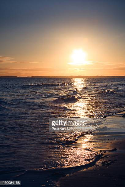 Sunrise above surf by sea